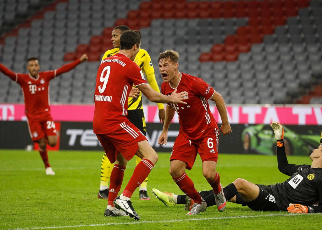 Joshua Kimmich und Robert Lewandowski vom FC Bayern jubeln vor Dortmunder Spielern.